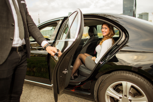 Chauffeur holding car door for a businesswoman